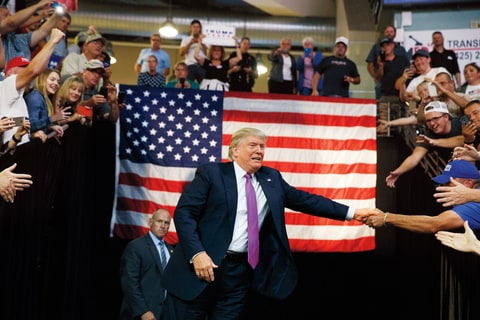 Republican presidential candidate Donald Trump shakes hands as he arrives to a campaign rally at Xfinity Arena of Everett, Tuesday, Aug. 30, 2016, in Everett, Wash.