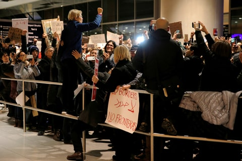 Sen. Elizabeth Warren of Massachusetts stands on a railing to address demonstrators at Logan Airport in January.