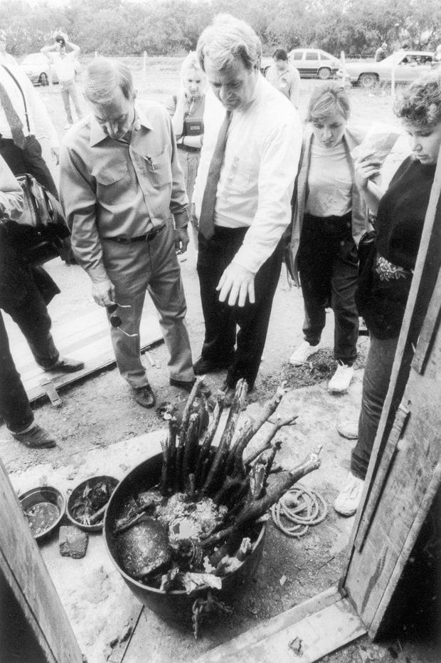 Texas Attorney General Jim Mattox (white shirt, center) views cauldron of bones found at ranch where 12 bodies were found buried including the body of U.S. college student Mark Kilroy. Bettmann/Getty
