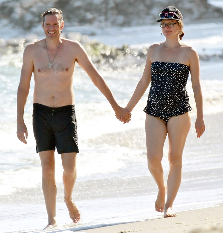 Milla Jovovich Takes Her Baby Bump to the Beach in a Dotted Swimsuit — See the Cute Picture!