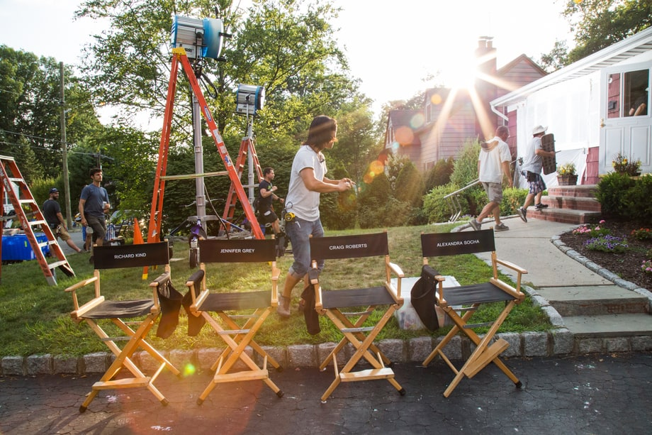 'Red Oaks' crew member takes a photo from the cast's chairs