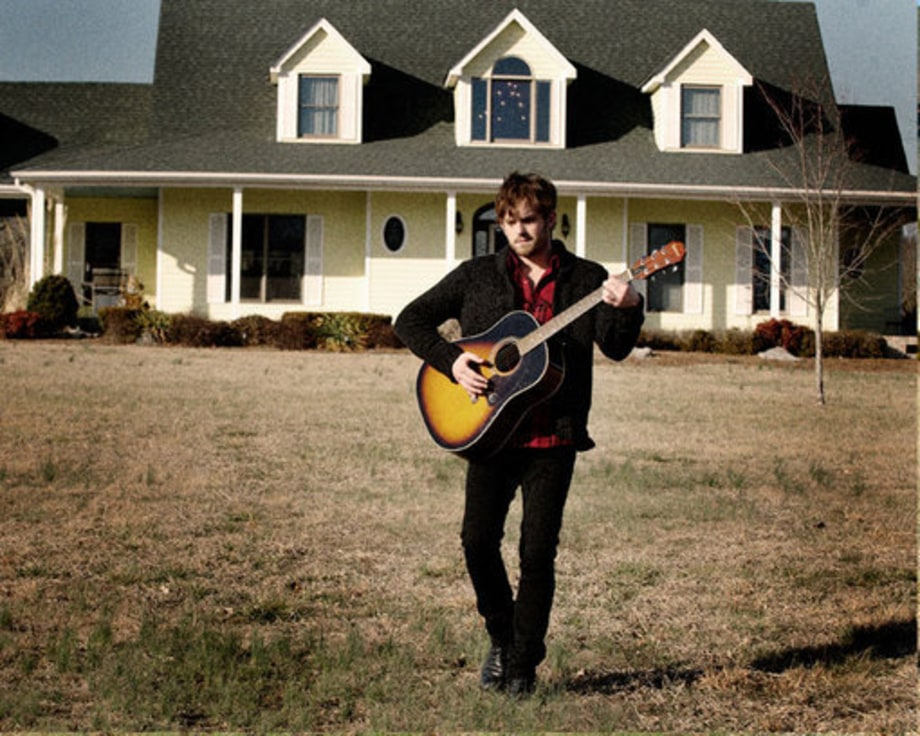 Caleb Followill Playing Guitar In Front of House