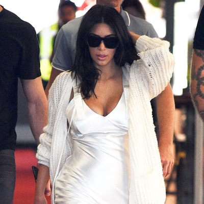 Kim Kardashian Arrives in Cannes Wearing Slinky White Slip Dress, Thigh-High Boots