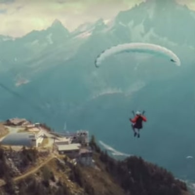 Watch a Paraglider Fly Into a Moving Cable Car